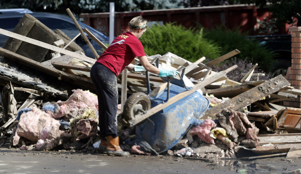 Photo - A woman dumps a wheel barrel full of flood damaged property into a trash pile as residents cleanup their homes in Longmont, Colo., on Thursday, Sept. 19, 2013. Rescuers continued efforts to reach stranded victims, while electricity and phone services were being restored to ravaged areas, allowing residents to contact family, friends or authorities. (AP Photo/Ed Andrieski)