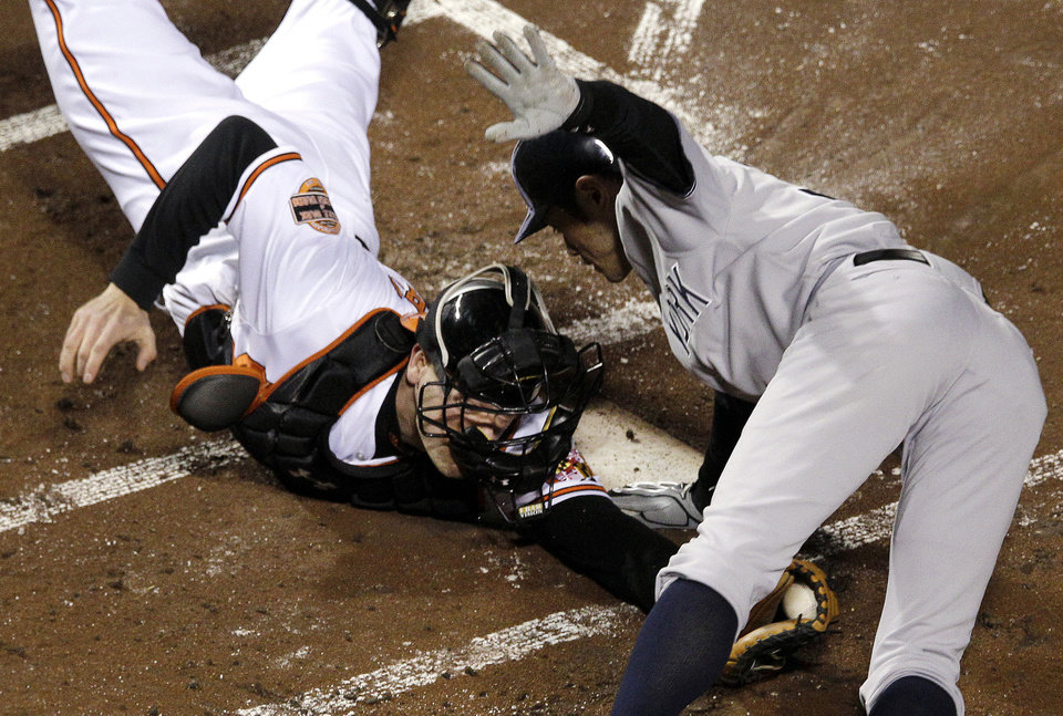 New York Yankees\' Ichiro Suzuki, right, of Japan, leaps past Baltimore Orioles catcher Matt Wieters to score a run on a double by Robinson Cano in the first inning of Game 2 of the American League division baseball series on Monday, Oct. 8, 2012, in Baltimore. (AP Photo/Patrick Semansky)