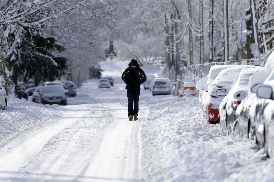 Photo - A pedestrian makes their way along a snow packed street in Indianapolis Monday, Jan. 6, 2014 as temperatures hovered around 10 below zero. More than 12 inches of snow fell on Sunday. (AP Photo/Michael Conroy)