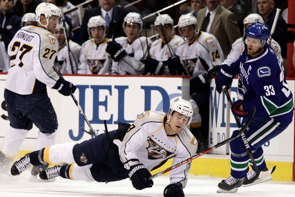Nashville Predators' Colin Wilson, center, is tripped by Vancouver Canucks' Henrik Sedin (33), of Sweden, as Nashville's Patric Hornqvist, left, alsoof Sweden, looks on during the first period of an NHL hockey game in Vancouver, British Columbia, on Wednesday, Jan. 26, 2011. (AP Photo/The Canadian Press, Darryl Dyck)
