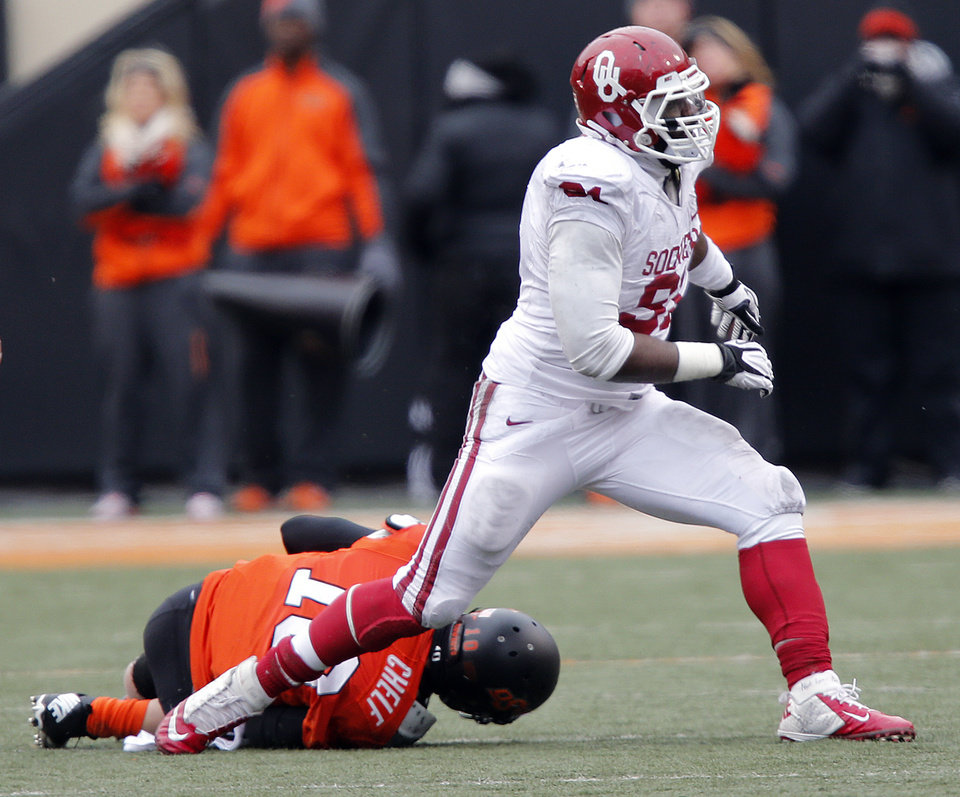 Photo - Oklahoma's Charles Tapper (91) reacts after a sack on Oklahoma State's Clint Chelf (10) during the Bedlam college football game between the Oklahoma State University Cowboys (OSU) and the University of Oklahoma Sooners (OU) at Boone Pickens Stadium in Stillwater, Okla., Saturday, Dec. 7, 2013. Photo by Chris Landsberger, The Oklahoman