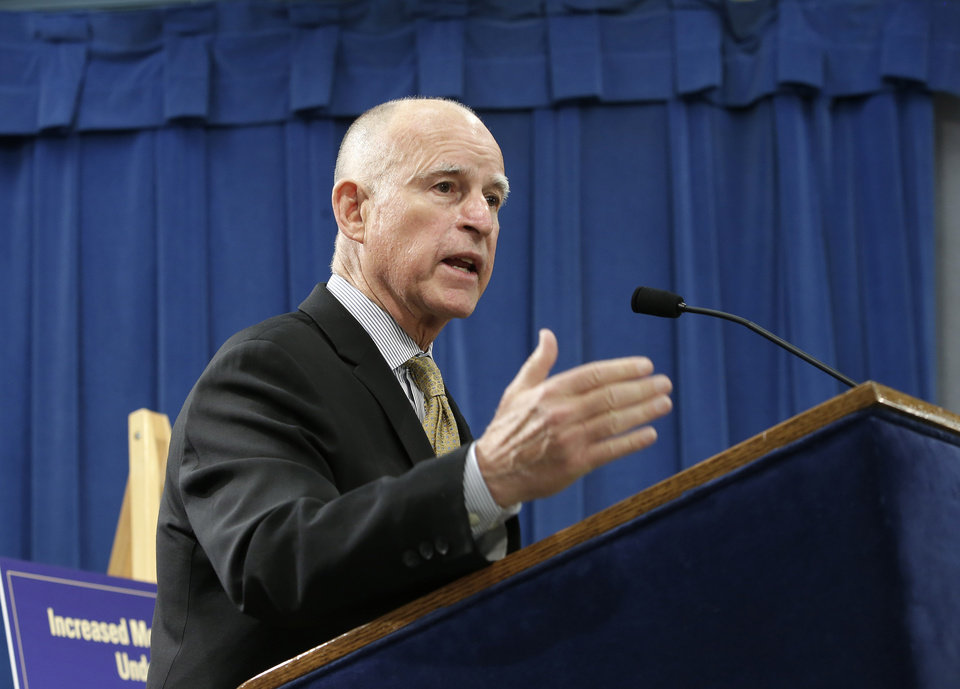 Photo - Gov. Jerry Brown responds to a question about his revised 2014-15 state budget that he unveiled at the Capitol news conference in  Sacramento, Calif., Tuesday, May 13, 2014.  Brown's revised spending plan projects  $107.7 billion in general fund spending, which is nearly $1 billion more than the budget Brown proposed in January.(AP Photo)