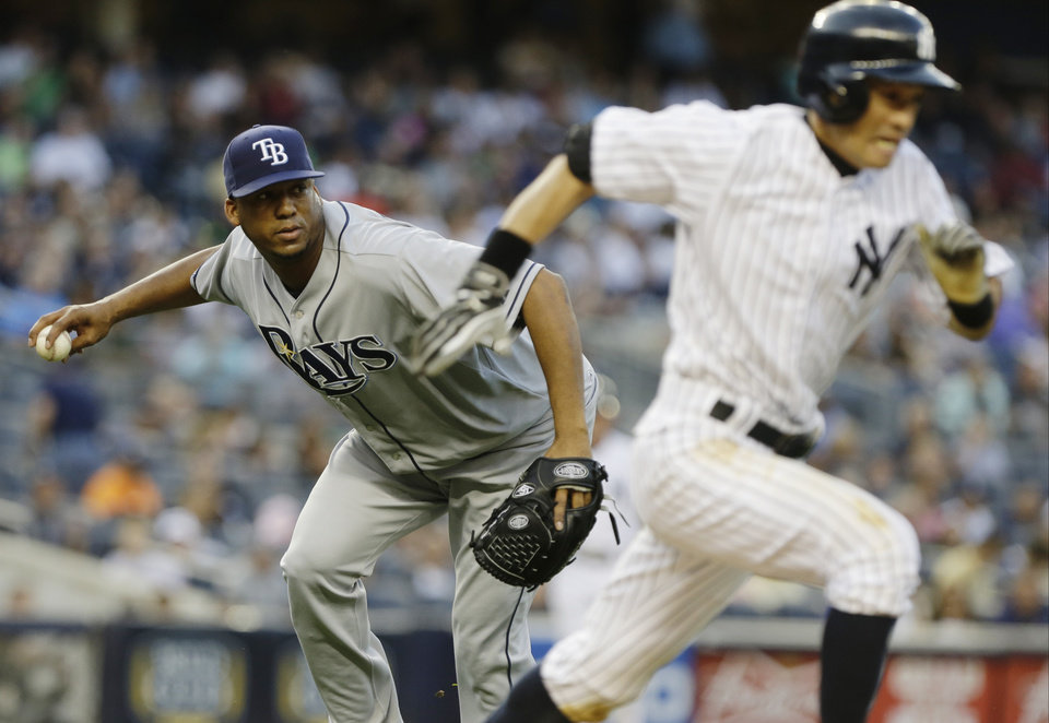 Tampa Bay Rays starting pitcher Roberto Hernandez, left, throws out New York Yankees' Ichiro Suzuki, right, of Japan, at first base during the third inning of a baseball game on Friday, June 21, 2013, in New York. A runner scored on the play. (AP Photo/Frank Franklin II)