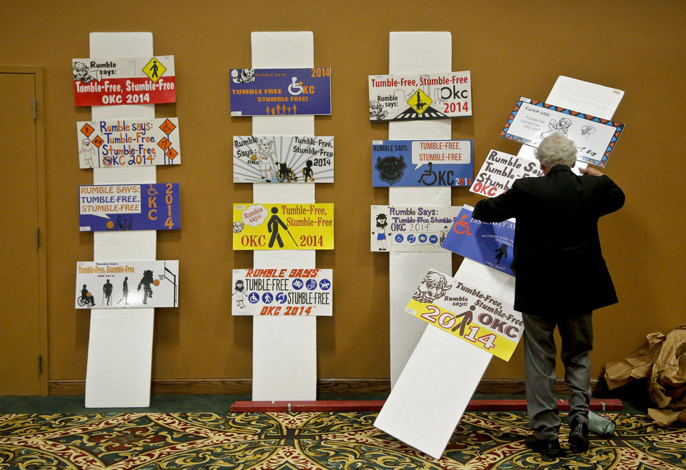 Photo - Dr. Henry Asin arranges some of the posters honored in the poster contest Tuesday during the 23rd annual Mayor's Committee on Disability Concerns awards at St. Luke's United Methodist Church. Photo by Chris Landsberger, The Oklahoman  CHRIS LANDSBERGER