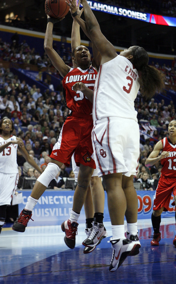 Photo - Courtney Paris blocks a shot by Angel McCoughtry in the first half as the University of Oklahoma plays Louisville at the 2009 NCAA women's basketball tournament Final Four in the Scottrade Center in Saint Louis, Missouri on Sunday, April 5, 2009. 