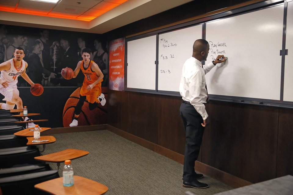 Photo - Mike Boynton writes on a board in a team meeting room Wednesday. [Bryan Terry/The Oklahoman]