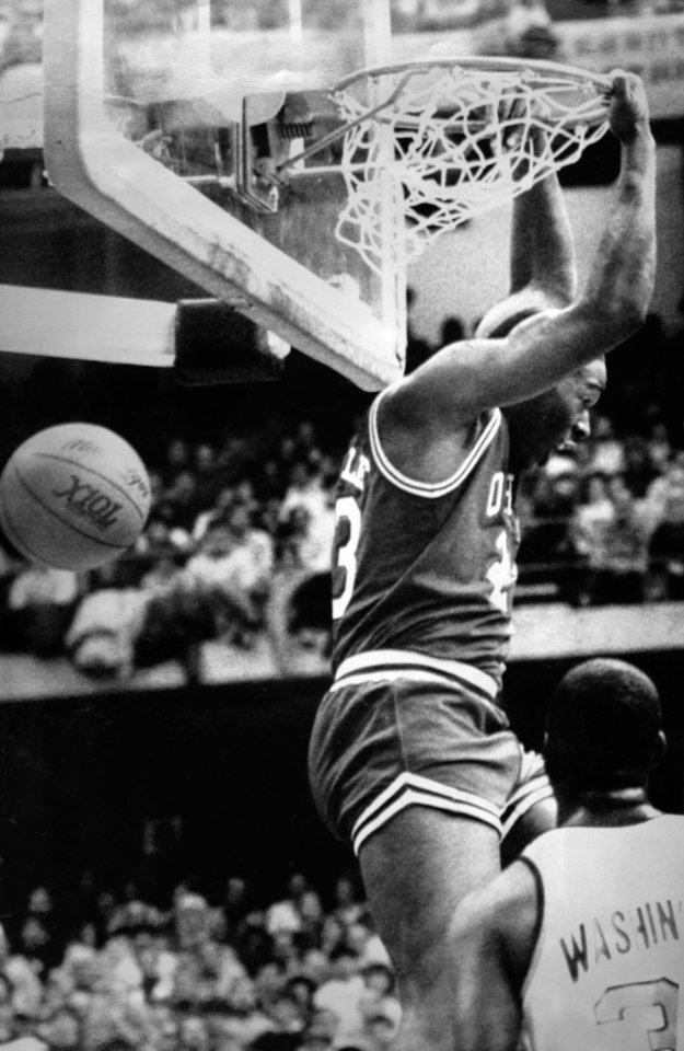 Photo - Former OU basketball player Wayman Tisdale. On a feed from Tim McCalister, OU's Wayman Tisdale slams through two of his 33 points during the Sooners' 98-91 victory over the Syracuse Orangemen on Saturday. (AP LaserPhoto) Photo taken unknown, Photo published 1/1/1984 in The Daily Oklahoman. ORG XMIT: KOD