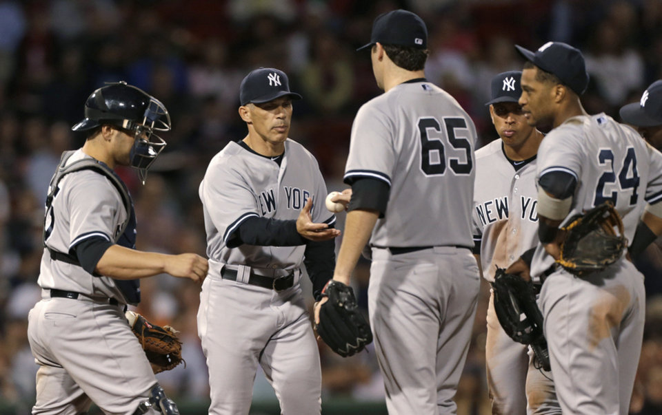 Photo -   New York Yankees starting pitcher Phil Hughes hands the ball to manager Joe Girardi in the eighth inning of a baseball game against the Boston Red Sox, Thursday, Sept. 13, 2012, at Fenway Park in Boston. Hughes allowed no runs and five hits, and struck out seven. (AP Photo/Charles Krupa)