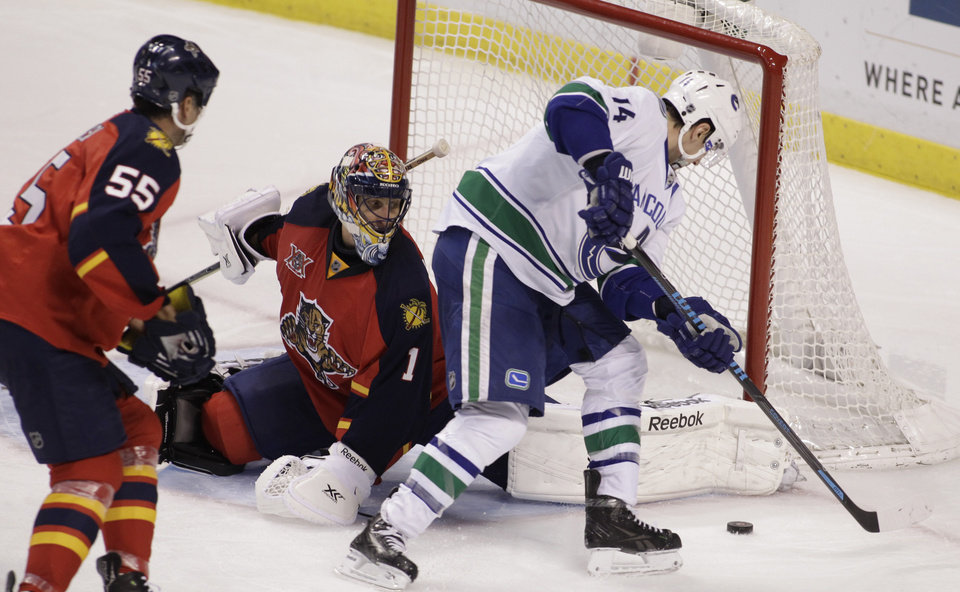 Photo - Vancouver Canucks'  Alexandre Burrows (14) scores a goal against Florida Panthers goalkeeper Roberto Luongo (1) as Panthers' Ed Jovanovski (55) looks on during the third period of an NHL hockey game on Sunday, March 16, 2014, in Sunrise, Fla.  The Canucks won 4-3 in a shootout. (AP Photo/Luis M. Alvarez)