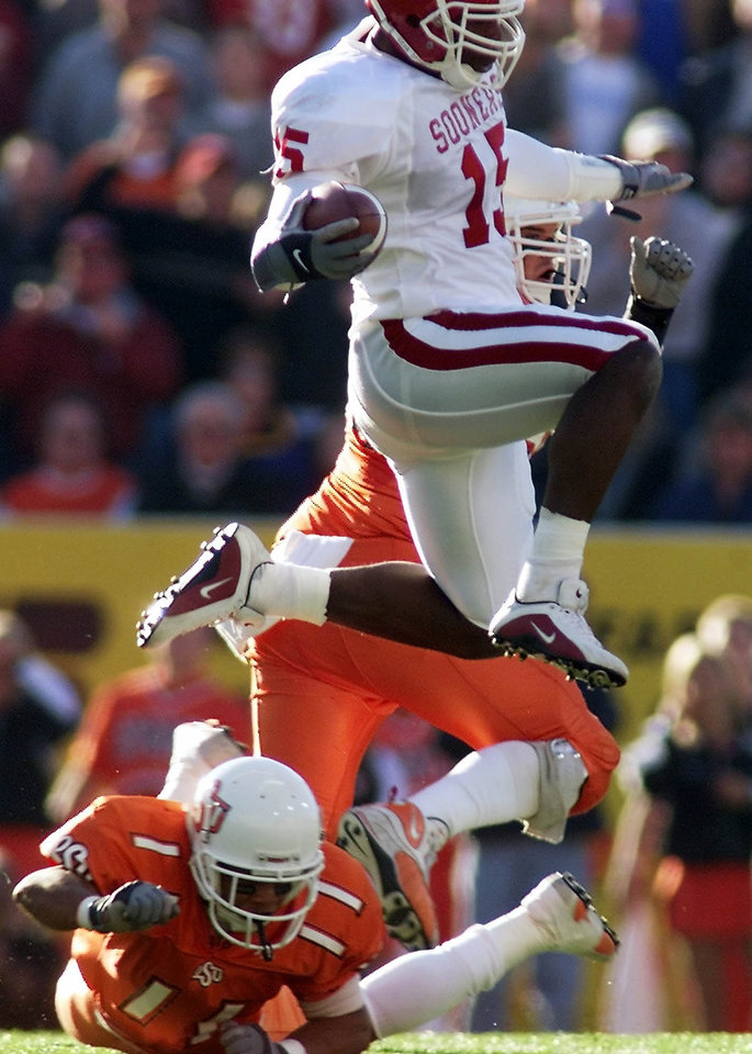 OU vs OSU football in Stillwater. OU's J.T. Thatcher leaps over Gabe Lindsay on his return after an interception. Staff Photo by Doug Hoke.