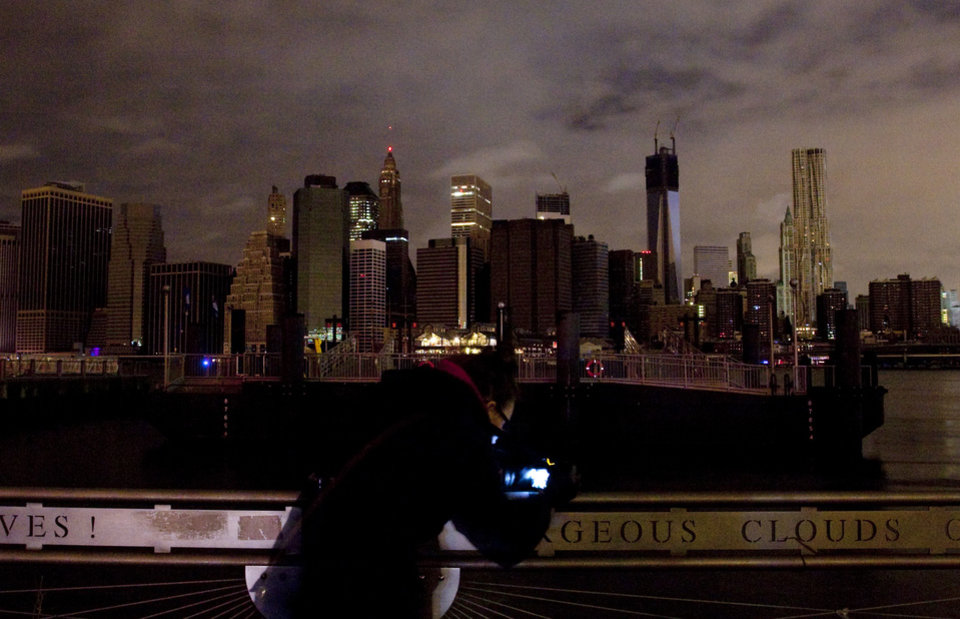 A woman photographs the Manhattan skyline, Tuesday, Oct. 30, 2012 in New York. Much of lower Manhattan is without electric power following the impact of superstorm Sandy. (AP Photo/Mark Lennihan) ORG XMIT: NYML123