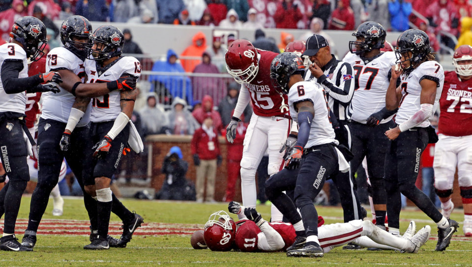 Photo - Oklahoma's Dede Westbrook (11) lays on the turf following a hit by Oklahoma State's Jordan Sterns (13) during the Bedlam college football game between the Oklahoma Sooners (OU) and the Oklahoma State Cowboys (OSU) at Gaylord Family - Oklahoma Memorial Stadium in Norman, Okla., Saturday, Dec. 3, 2016. Photo by Steve Sisney, The Oklahoman