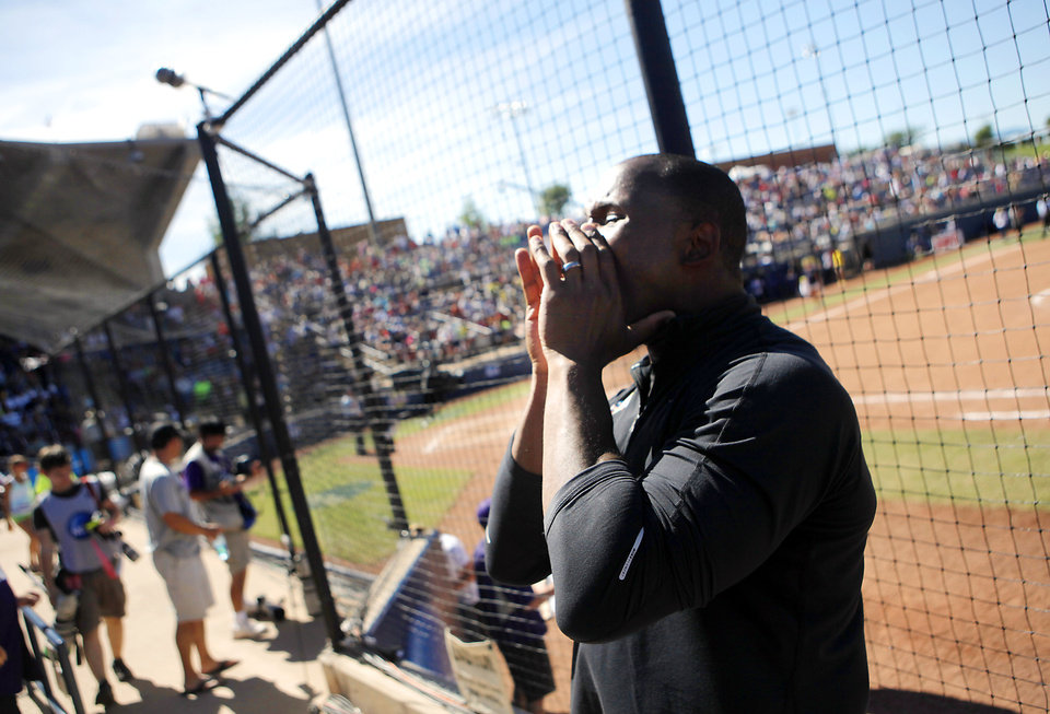 Photo - Washington strength coach Keith Belton leads cheers for the Huskies fans in the Women's College World Series elimination game versus Michigan. The Washington Huskies would go on to win 4-1. Photo by KT KING, The Oklahoman