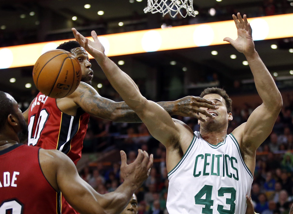 Photo - Boston Celtics center Kris Humphries (43) cannot control a rebound against Miami Heat forward Udonis Haslem (40) and guard Dwyane Wade (3) in the first quarter of an NBA basketball game in Boston Wednesday, March 19, 2014. (AP Photo/Elise Amendola)