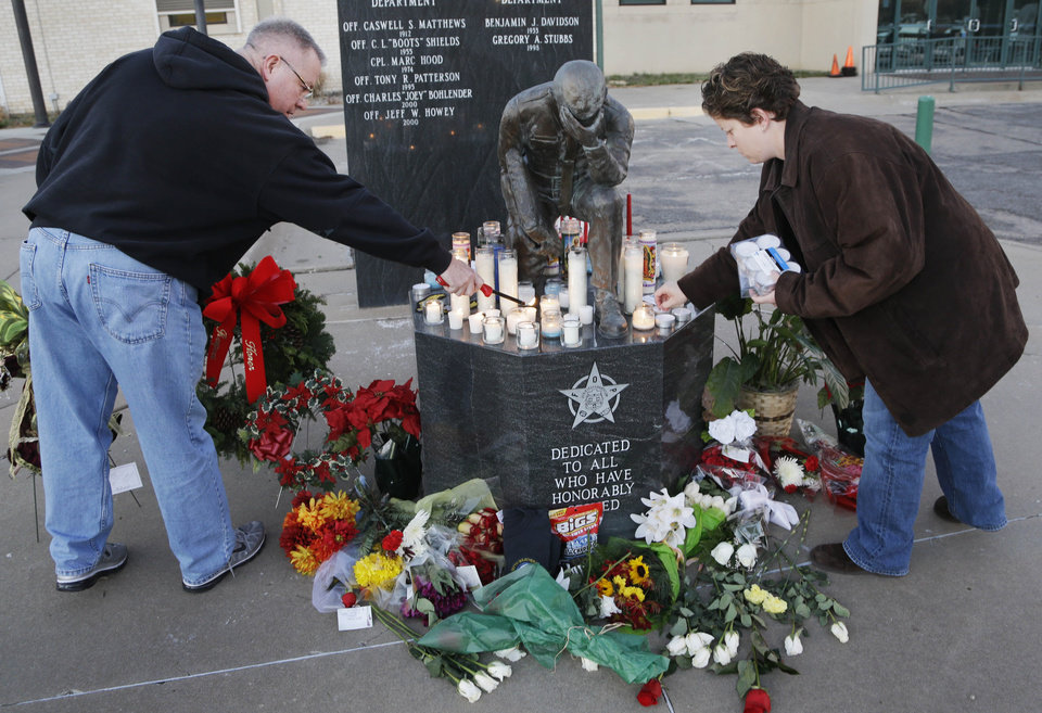 Photo - Topeka Police Lt. Jack Mackey, left, and Jennifer Walker light candles in honor of two officers killed in the line of duty in Topeka, Kan., Monday, Dec. 17, 2012. A man with a history of theft and weapons convictions gunned down two police officers investigating possible drug activity in a Kansas grocery parking lot, and was later killed after an armed standoff, authorities said Monday. (AP Photo/Orlin Wagner)