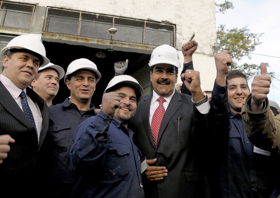 Photo - Venezuela's President Nicolas Maduro, second from right in red tie, poses for photos with factory workers at Urutransfor, which makes transformers, in Montevideo, Uruguay, Tuesday, May 7, 2013. Maduro is on a one-day official visit to Uruguay. (AP Photo/Matilde Campodonico)