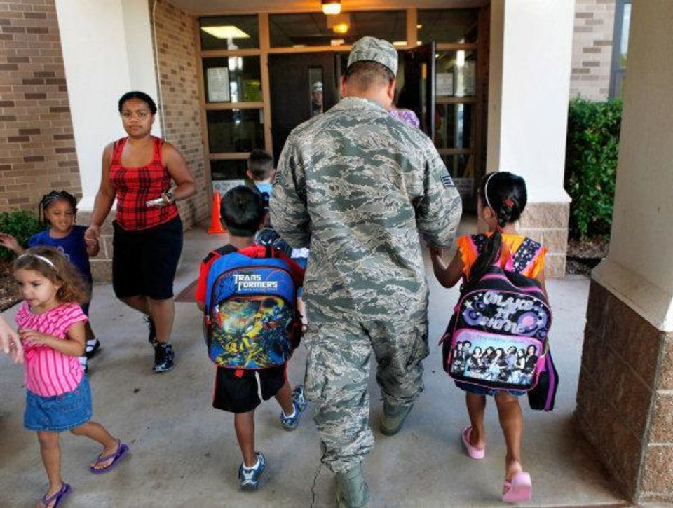 Photo - Ssgt. Wedler Harry, Jr. (USAF) walks his children into Tinker Elementary School on FridayHis son, Jared, is in the first grade. His daughter,  Maranatha, is in the 2nd grade. Sixty percent of the school's students come from military families, and school officials are intune to students with parents who are deployed.  JIM BECKEL - THE OKLAHOMAN