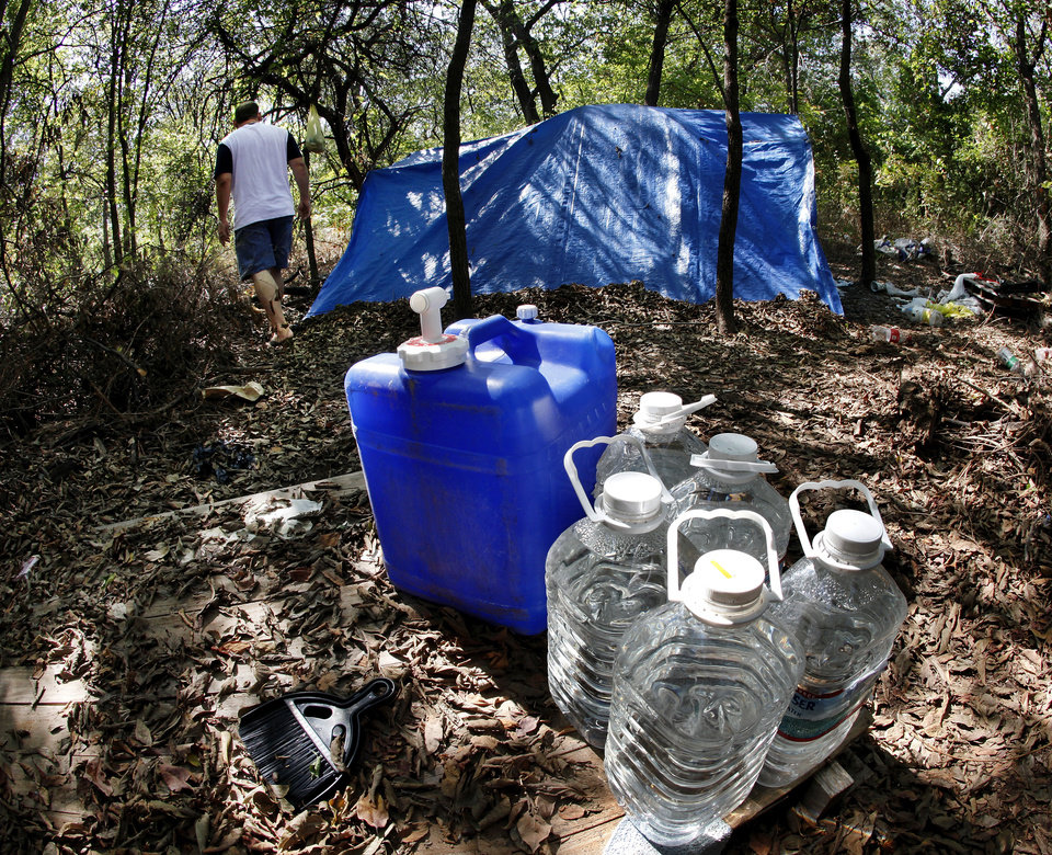 Photo - Jeff Wendel, staff member at Hand Up Ministry, walks Wednesday,  Aug. 29, 2012, among tents and mattresses used by men who were former residents at the ministry's campus on SE 59. A number of men have been forced to leave the trailers there and now live in a wooded area in the southeast part of Oklahoma County. Photo by Jim Beckel  Jim Beckel - THE OKLAHOMAN