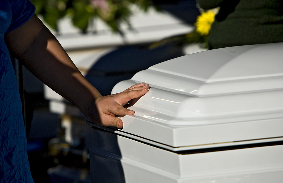 A mourner place a hand on one of the five caskets during graveside services of Summer Rust and her four children Kirsten Rust, Autumn Rust, Teagin Rust and Evynn Garas in El Reno, Okla. on Wednesday, Jan. 21, 2009. Rust and her children were killed earlier this month in their apartment in El Reno, Okla. 