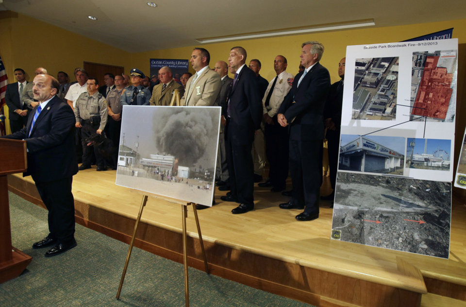 Photo - Ocean County Prosecutor Joseph D. Coronato, left, stands in front of investigators and photos in Toms River, N.J., Tuesday, Sept. 17, 2013, as he answers a question about the boardwalk fire in Seaside Park and Seaside Heights last Thursday.   Coronato said the massive boardwalk fire was accidental and linked it to electrical wiring and equipment that was compromised by Superstorm Sandy nearly a year ago.  Investigators say the fire, which destroyed more than 50 boardwalk businesses, started under a building that housed a candy store and an ice cream stand. (AP Photo/Mel Evans)