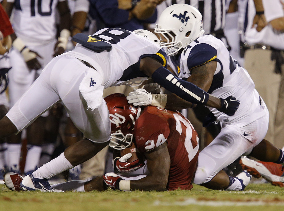 Photo - Oklahoma's Brennan Clay (24) slides down as West Virginia's Karl Joseph (8) collide with West Virginia's Doug Rigg (47) during a college football game between the University of Oklahoma Sooners (OU) and the West Virginia University Mountaineers at Gaylord Family-Oklahoma Memorial Stadium in Norman, Okla., on Saturday, Sept. 7, 2013. Rigg was injured on the play. Oklahoma won 16-7. Photo by Bryan Terry, The Oklahoman