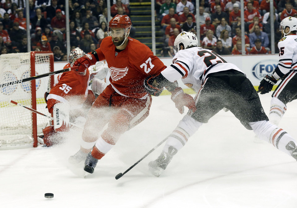 Photo - Detroit Red Wings defenseman Kyle Quincey (27) and Chicago Blackhawks left wing Brandon Saad (20) battle for the puck during the first period in Game 4 of the Western Conference semifinals in the NHL hockey Stanley Cup playoffs in Detroit, Thursday, May 23, 2013. (AP Photo/Paul Sancya)