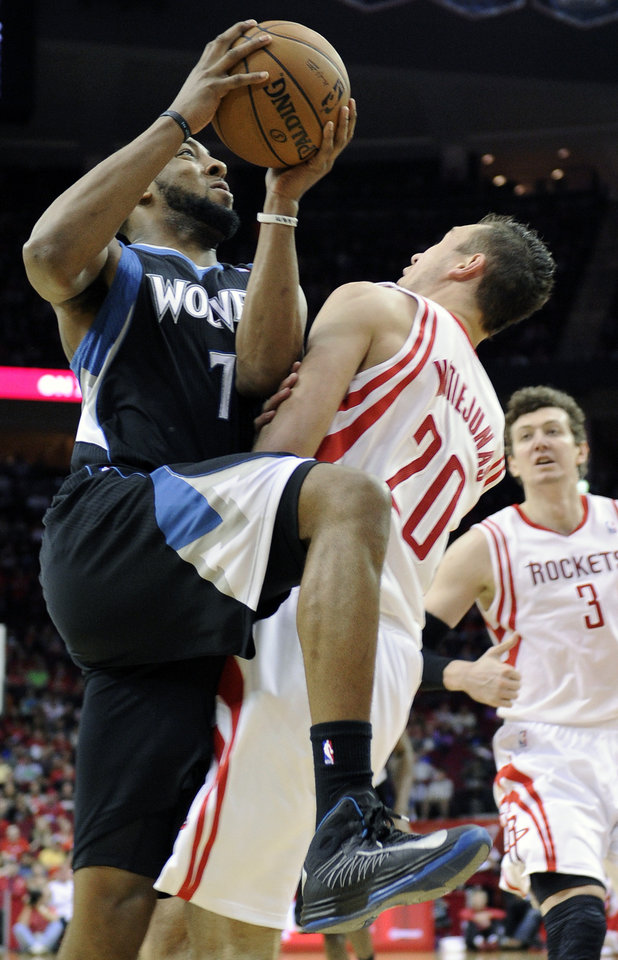 Photo - Minnesota Timberwolves' Derrick Williams (7) commits an offensive foul against Houston Rockets' Donatas Motiejunas (20) in the first half of an NBA basketball game Friday, March 15, 2013, in Houston. (AP Photo/Pat Sullivan)
