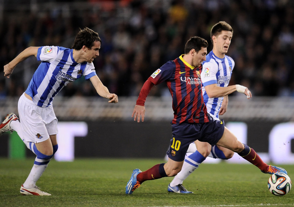 Photo - FC Barcelona's Lionel Messi of Argentina, center, goes for the ball between Real Sociedad's Jon Gaztanaga, right, and Mikel Gonzalez, left, before to scoring his goal, during their Spanish Copa del Rey semifinal second leg soccer match, at Anoeta stadium, in San Sebastian northern Spain, Wednesday, Feb. 12, 2014. (AP Photo/Alvaro Barrientos)