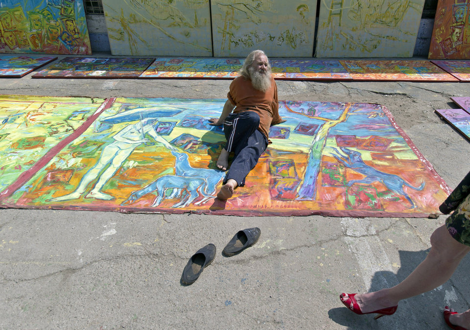 Photo - In this photo taken on April 4, 2013, Romanian artist Vasile Muresan, known as Murivale sits on one of his paintings in a parking lot,  in Bucharest, Romania. The white-bearded painter can often be seen sitting on his colorful canvasses which he displays in the street followed by the street dogs which are his companions and also inspire his work. The 56-year-old, whose home city is Bistrita_the Transylvanian town associated with the legendary Count Dracula_ has been painting with passion since he was a teen, producing vivid works of Monaco, the streets of Paris, the hurly burly of the Romanian capital and huge colorful more abstract canvasses. (AP Photo/Vadim Ghirda)