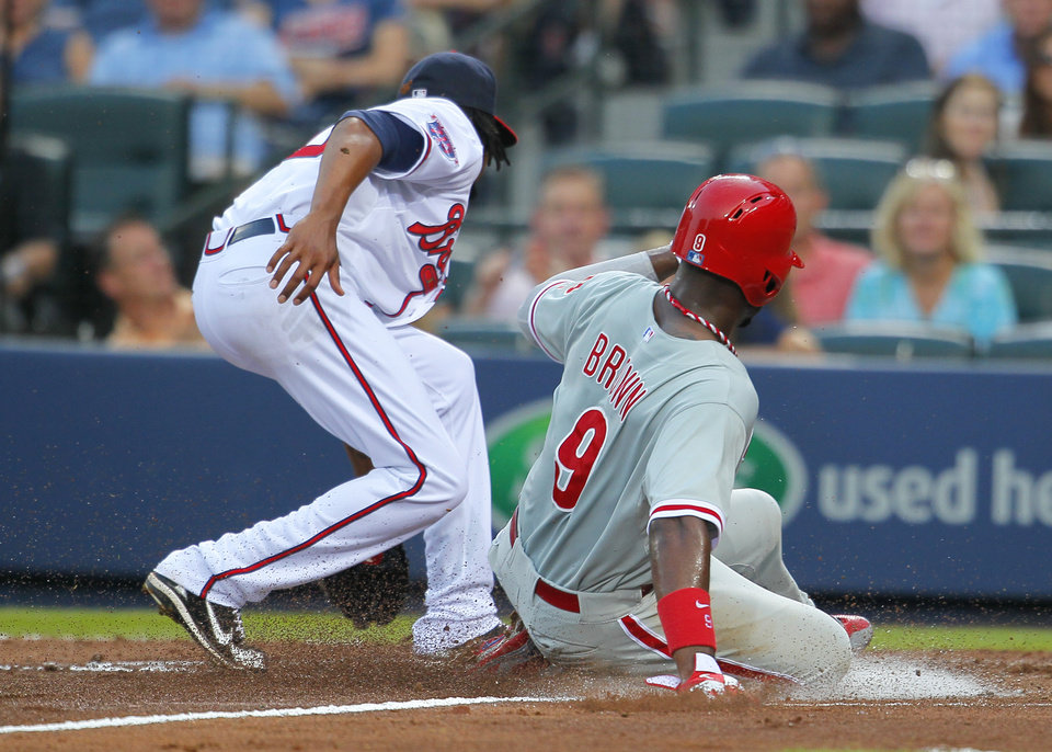 Photo - Philadelphia Phillies Domonic Brown, right, slides into home after a wild pitch by Atlanta Braves starting pitcher Ervin Santana, left, in the fourth inning of a baseball game Tuesday, June 17, 2014, in Atlanta. (AP Photo/Todd Kirkland)