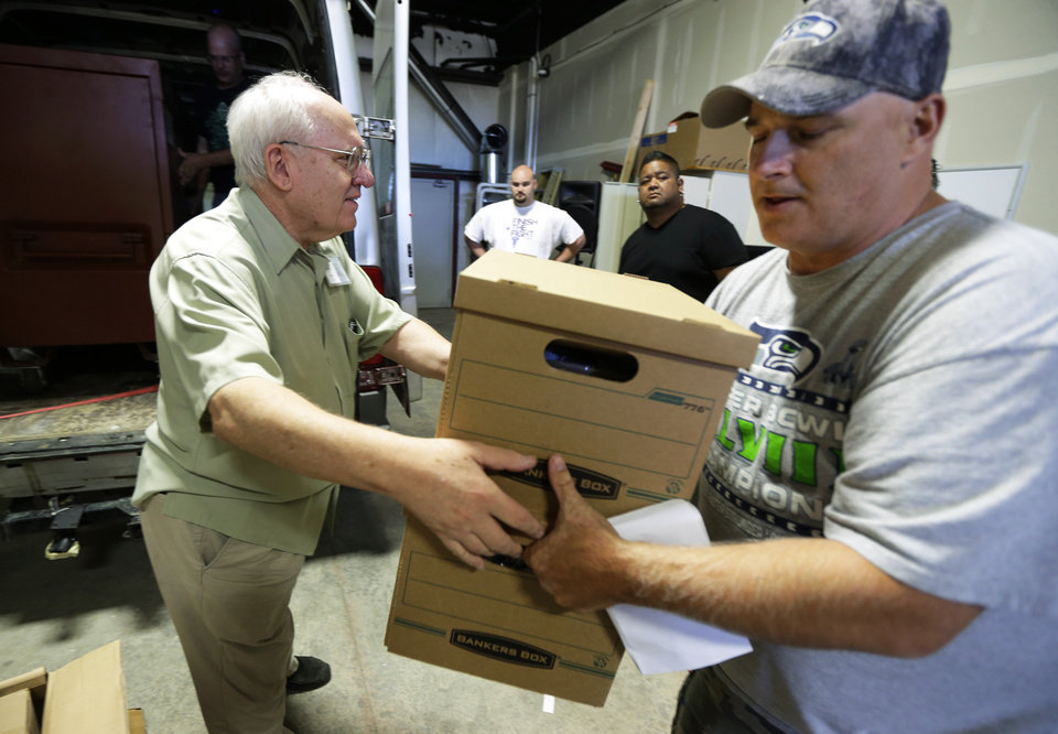 Photo - In this July 8, 2014, photo, the final step of the lengthy marijuana growing operation takes place as Bob Leeds, left, owner of Sea of Green Farms, hands boxes containing packaged recreational marijuana to Tom Beckley, right, the owner of Top Shelf Cannabis in Bellingham, Wash. (AP Photo/Ted S. Warren)