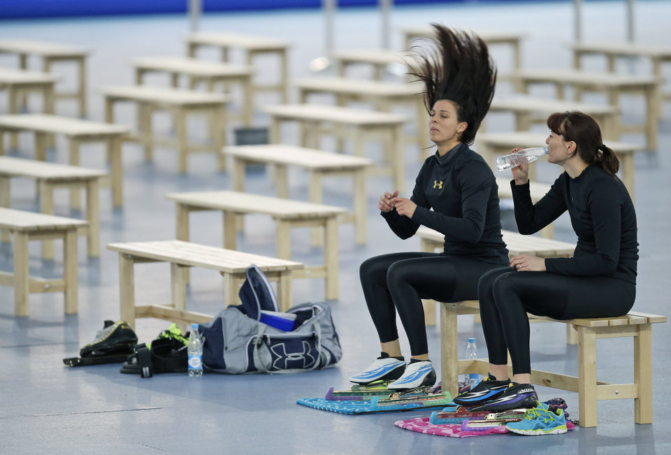 Photo - Brittany Bowe of the U.S. unties her hair sitting next Heather Richardson of the U.S., right, after practicing at the Adler Arena Skating Center at the 2014 Winter Olympics, Saturday, Feb. 15, 2014, in Sochi, Russia. (AP Photo/Pavel Golovkin)