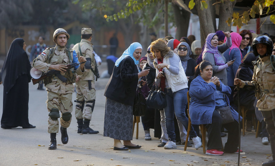 Photo - Egyptian army soldiers stand guard as voters line up outside a polling station in Cairo, Egypt, Tuesday, Jan. 14, 2014. Egyptians have started voting on a draft for their country's new constitution that represents a key milestone in a military-backed roadmap put in place after President Mohammed Morsi was overthrown in a popularly backed coup last July. (AP Photo/Amr Nabil)