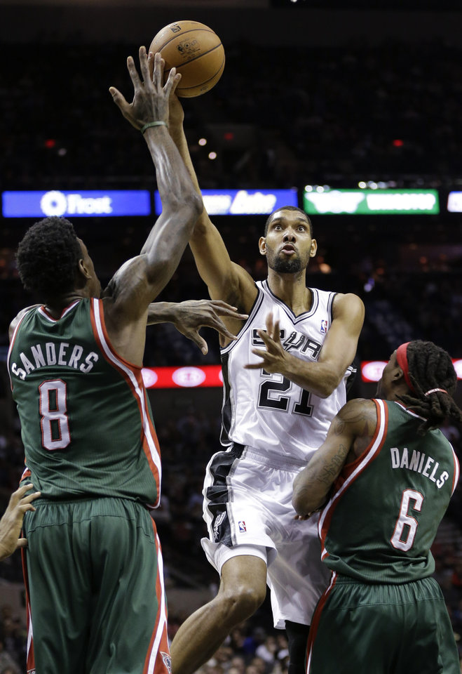 San Antonio Spurs' Tim Duncan (21) drives between Milwaukee Bucks' Larry Sanders (8) and Marquis Daniels (6) during the first quarter of an NBA basketball game on Wednesday, Dec. 5, 2012, in San Antonio. San Antonio won 99-95. (AP Photo/Eric Gay)