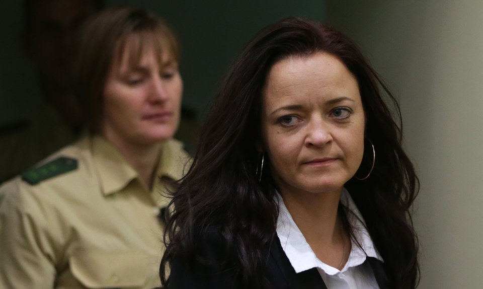 Photo - FILE - In this June 11, 2013 file picture  Beate Zschaepe,, right,  alleged member of the neo-Nazi group National Socialist Underground, NSU, enters a court room in Munich, southern Germany,  A  nearly 1,400-page report released Thursday Aug. 22, 2013  follows a 19-month review of how police and intelligence agencies failed to stop the National Socialist Underground group killing eight Turks, a Greek and a policewoman between 2000 and 2007. The group was only linked to the killings after two main members died in a murder-suicide after a botched 2011 bank robbery. The third suspected main member is now on trial. The cross-party committee says authorities didn't properly consider the possibility that the killings were racially motivated, partly because of their own biases. It calls for more minorities in the security services.    (AP Photo/Matthias Schrader, File)