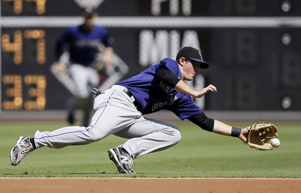 Photo -   Colorado Rockies second baseman DJ LeMahieu dives for a ground out by Philadelphia Phillies' Nate Schierholtz in the first inning of the first game of a baseball doubleheader, Sunday, Sept. 9, 2012, in Philadelphia. (AP Photo/Matt Slocum)