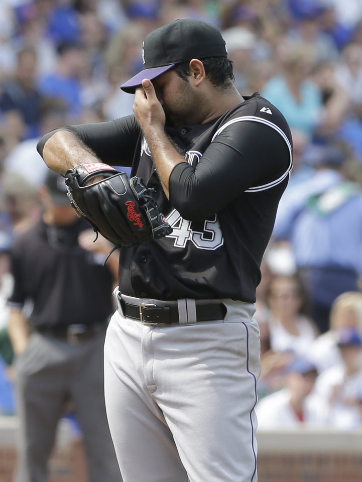 Photo - Colorado Rockies starter Pedro Hernandez wipes his face after Chicago Cubs' Anthony Rizzo walked to first base during the sixth inning of a baseball game in Chicago, Thursday, July 31, 2014. (AP Photo/Nam Y. Huh)