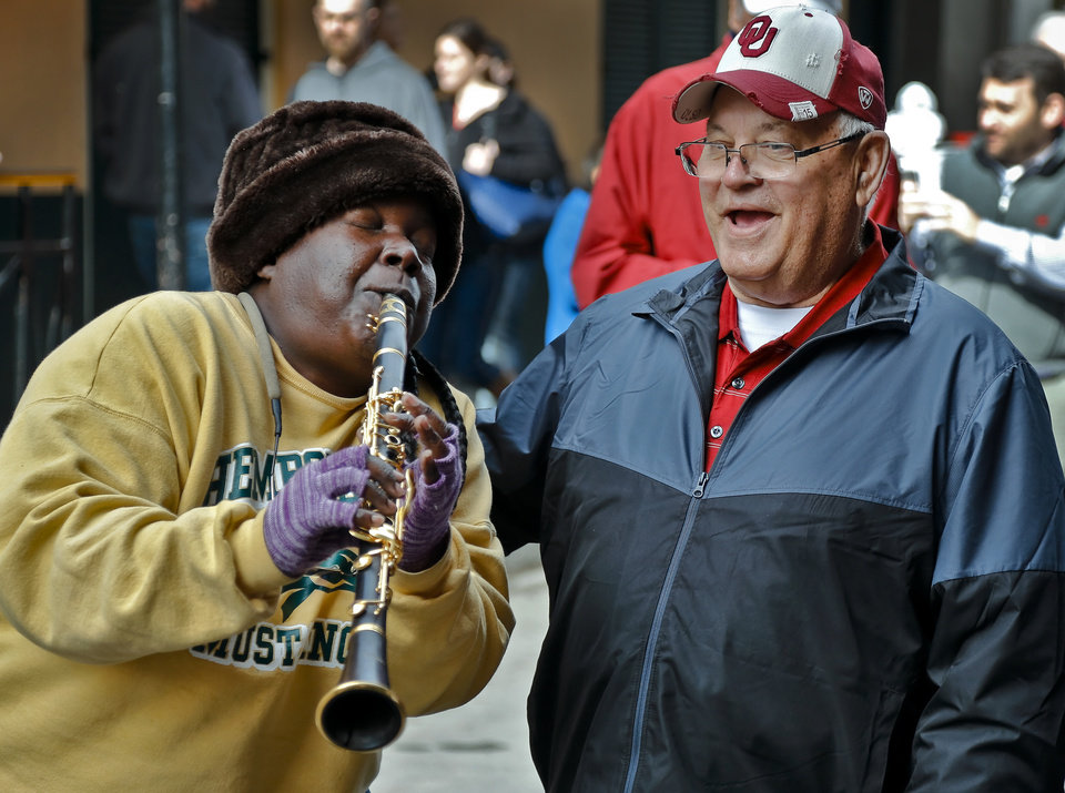 Photo - Street musician Doreen J. Ketchens of Doreen's Jazz band plays happy birthday to Sooner fan Jerry Kendall on the streets of the French Quarter before the start of the NCAA football BCS Sugar Bowl game between the University of Oklahoma Sooners (OU) and the University of Alabama Crimson Tide (UA) at the Superdome in New Orleans, La., Thursday, Jan. 2, 2014. Kendall turns 73 on Friday, and is the great uncle to Oklahoma quarterback Blake Bell. Photo by Chris Landsberger, The Oklahoman