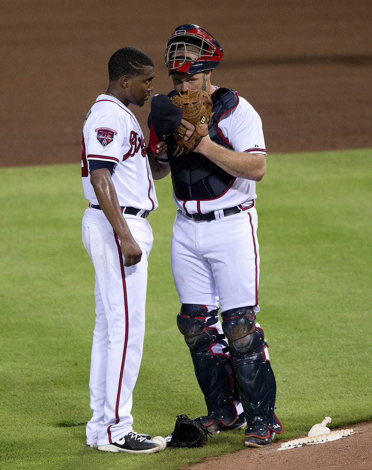 Photo - Atlanta Braves starting pitcher Julio Teheran (49) and catcher Evan Gattis (24) talk on the mound during the sixth inning of a baseball game against the Los Angeles Dodgers  Monday, Aug. 11, 2014 in Atlanta.  (AP Photo/John Bazemore)