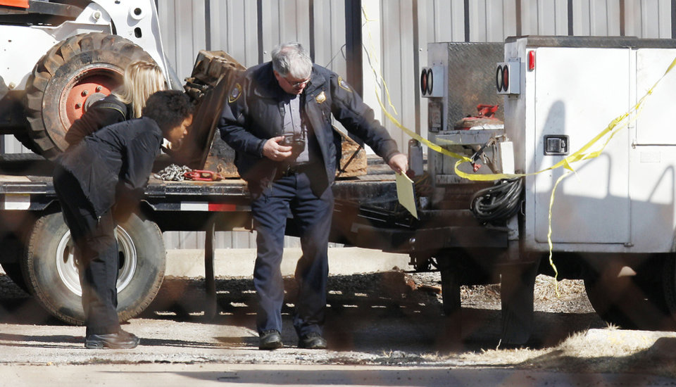 Oklahoma City police and the medical examiner�s office investigate the scene where a truck backed over a man Monday.  Photo by PAUL B. SOUTHERLAND, the Oklahoman