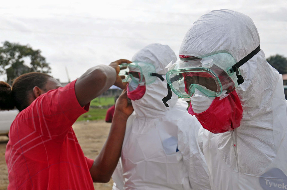 Photo - A health worker assists a colleague with his protective gear, as they collect the body of a man suspected to have died from the ebola virus, in Monrovia, Liberia,  Tuesday, Aug. 12, 2014. The World Health Organization declared it's ethical to use untested drugs and vaccines in the ongoing Ebola outbreak in West Africa although the tiny supply of one experimental drug handed out to three people has been depleted and it could be many months until more is available. (AP Photo/Abbas Dulleh)