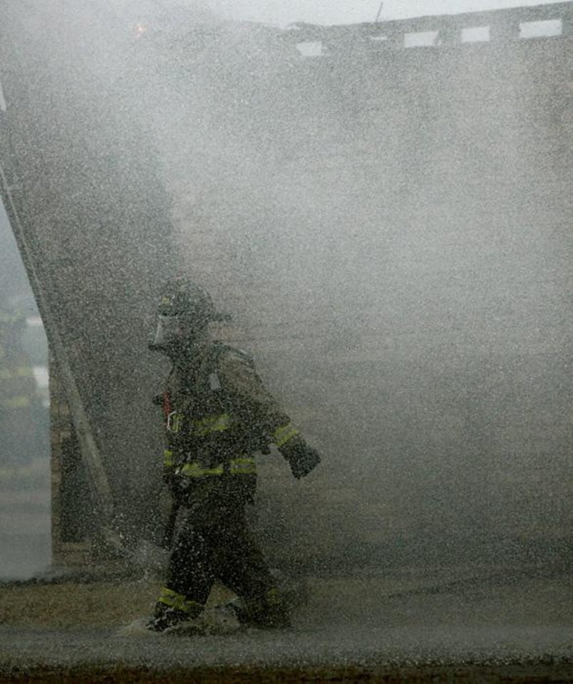 Photo -  Covered with water and smoke, an Oklahoma City firefighter works on a church fire in Spencer, Okla., on Wednesday, Feb. 10, 2010. Photo by John Clanton, The Oklahoman ORG XMIT: KOD
