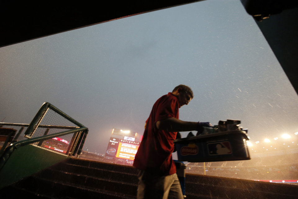 Photo - A clubhouse attendant cleans out the Miami Marlins dugout before a baseball game against the Washington Nationals at Nationals Park on Tuesday, May 27, 2014, in Washington. The game has been postponed due to weather. (AP Photo/Alex Brandon)