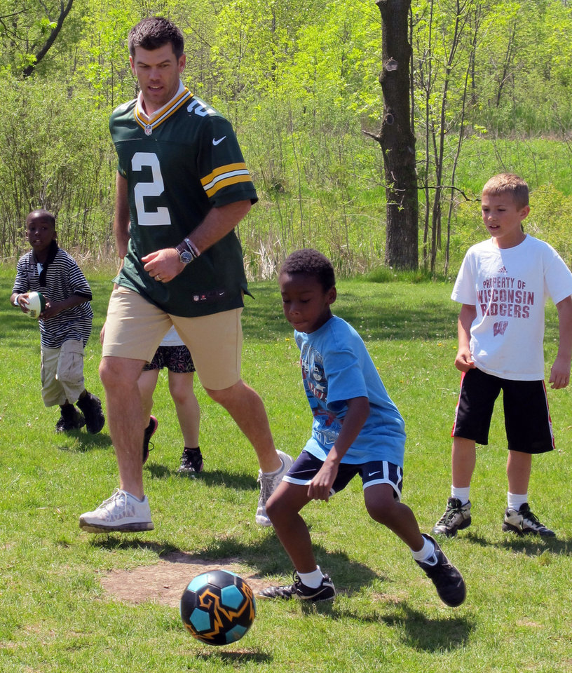 "Green Bay Packers kicker Mason Crosby plays soccer with students at Indian Hill School in Milwaukee on Friday, May 18, 2012, as part of the team's ""Tailgate Tour"" where they meet fans and raise money for charity. (AP Photo/Carrie Antlfinger)"