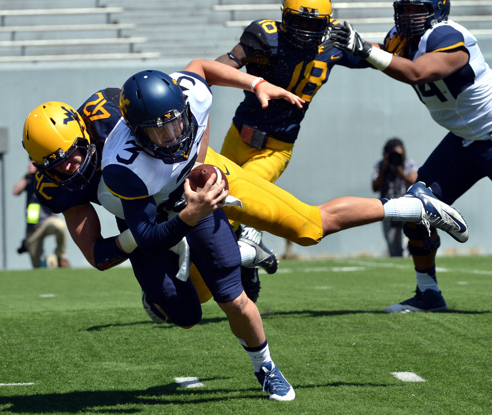 Photo - West Virginia quarterback Skyler Howard (3) is sacked by Houston Syvertson (42 during their spring NCAA college football game in Morgantown, W.Va., Saturday, April 12, 2014. (AP Photo/Craig Cunningham)