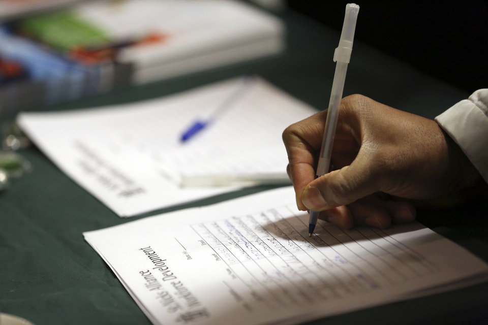 A job seeker leaves his contact information with a potential employer during a job fair in New York.   AP Photo