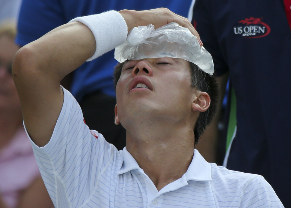 Photo - Kei Nishikori, of Japan, applies an ice pack to his forehead to cool down during a break between games against Stan Wawrinka, of Switzerland, during the quarterfinals of the 2014 U.S. Open tennis tournament, Wednesday, Sept. 3, 2014, in New York. (AP Photo/Mike Groll)