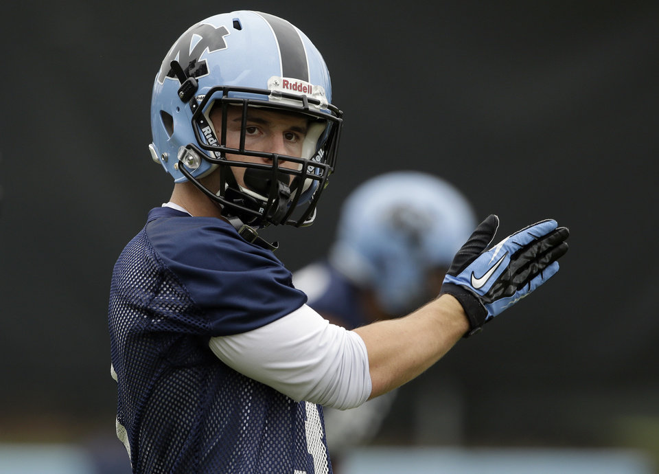 Photo - In this photo taken Friday, Aug. 1, 2014, North Carolina wide receiver Ryan Switzer signals a teammate during an NCAA football practice in Chapel Hill, N.C. (AP Photo/Gerry Broome)