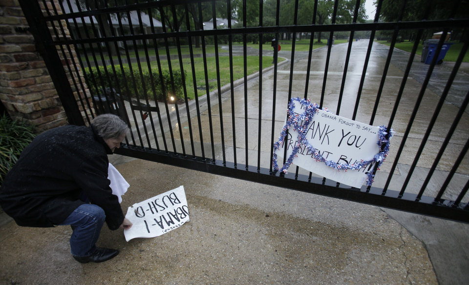 Photo - Glen Hunnter checks out a sign left in front of the gated Dallas neighborhood of former U.S. President George W. Bush in  Dallas, Texas, Monday, May 2, 2011. President Barack Obama announced Sunday night that Osama bin Laden was killed in an operation led by the United States.  (AP Photo/LM Otero) ORG XMIT: TXMO101
