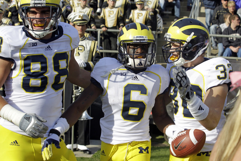 Photo -   Michigan defensive back Raymon Taylor, center, celebrates with defensive end Craig Roh, left, and safety Jordan Kovacs after scoring a touchdown on a 63-yard interception against Purdue during the first half of an NCAA college football game in West Lafayette, Ind., Saturday, Oct. 6, 2012. (AP Photo/Michael Conroy)